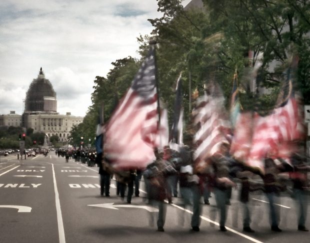 The United States Capital building sheathed in scaffolding as reenactors  in Union blue march up Pennsylvania Ave commemorating the Grand Review of the Armies in Washington DC 2015